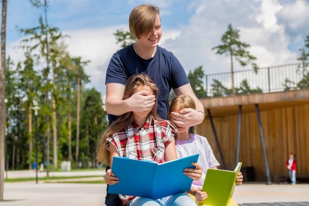 Duas adolescentes sentadas no banco e um menino fechando os olhos para uma menina
