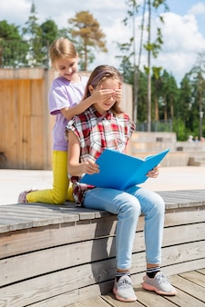 Duas adolescentes sentadas no banco uma atrás da outra, uma garota fechando os olhos para a outra.