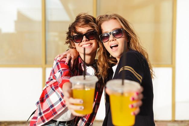 Duas adolescentes sorridentes em óculos de sol brindando
