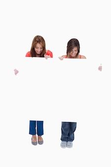 Duas adolescentes sorridentes enquanto olham para o poster em branco