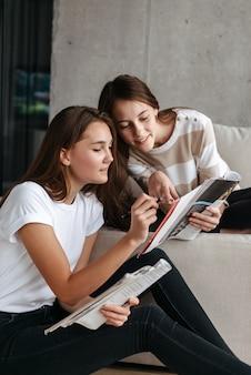 Duas adolescentes sorridentes lendo revistas enquanto estão sentadas em um sofá em casa