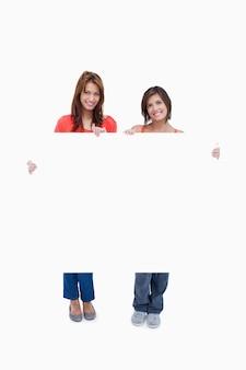 Duas adolescentes sorridentes segurando um cartaz em branco contra um fundo branco