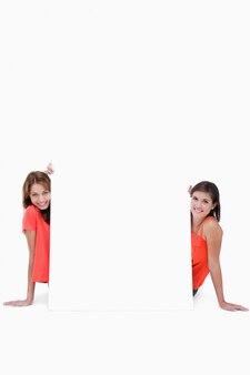 Duas adolescentes sorridentes sentadas atrás de um cartaz em branco
