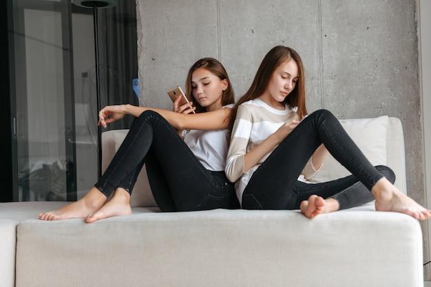 Duas adoráveis jovens adolescentes usando telefones celulares enquanto estão sentadas em um sofá em casa