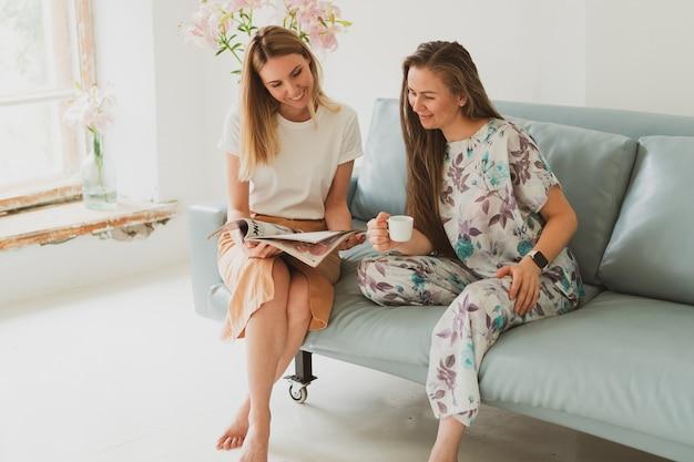 Duas adoráveis jovens conversando em casa no sofá, tomando café e vendo uma revista de moda