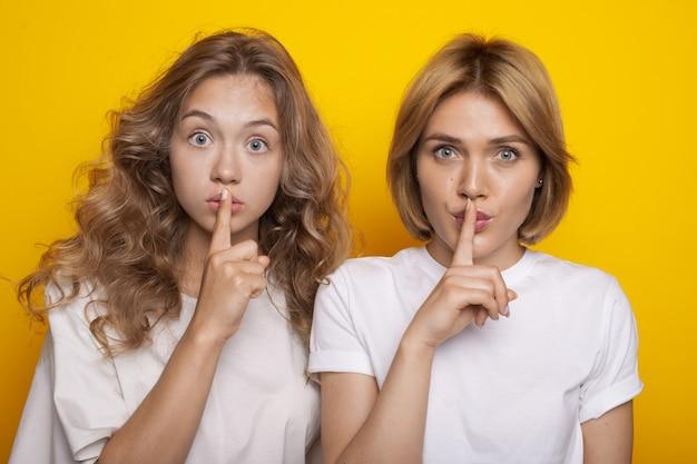 Duas adoráveis mulheres com cabelos loiros gesticulando o som do silêncio posando em uma parede amarela