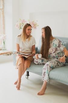 Duas adoráveis mulheres conversando em casa no sofá, tomando café e vendo uma revista de moda