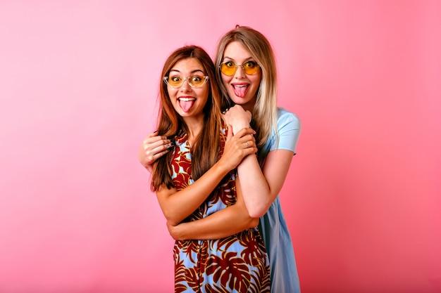Duas adoráveis mulheres jovens se divertindo, mostrando as línguas