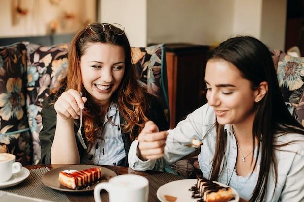 Duas adorável mulher sentada em um café comendo um bolo enquanto a história contando sorrindo, tendo um bom tempo.
