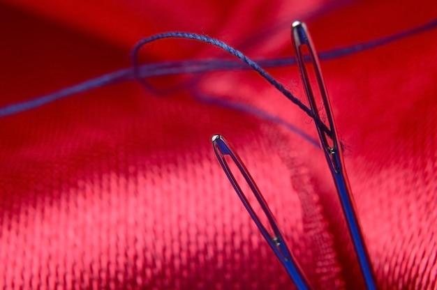 Duas agulhas de costura com linha azul sobre um fundo de tecido vermelho. fechar-se.