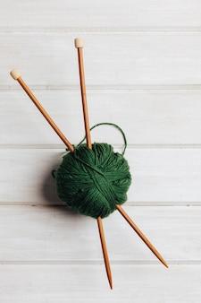 Duas agulhas de madeira em bola de lã