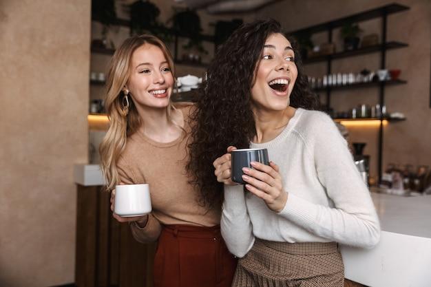 Duas alegres amigas jovens em pé no balcão do café, se divertindo juntas, bebendo café