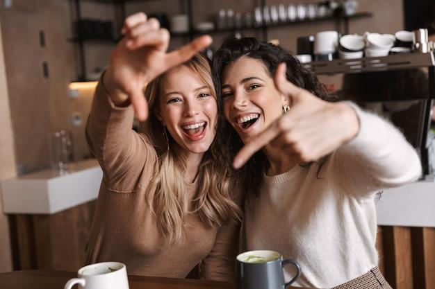 Duas alegres amigas jovens sentadas à mesa do café, se divertindo juntas, bebendo café