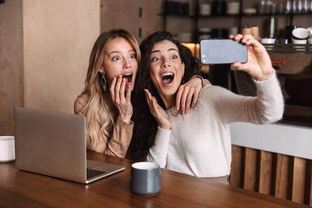 Duas alegres amigas jovens sentadas à mesa do café, se divertindo juntos, bebendo café, usando laptop, tirando uma selfie