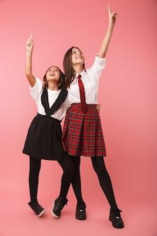 Duas alegres colegiais vestindo uniforme em pé, isoladas sobre uma parede rosa, apontando o dedo