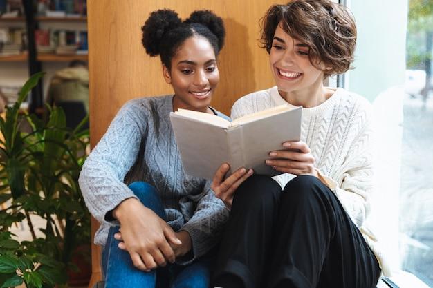 Duas alegres jovens estudantes estudando na biblioteca, lendo um livro juntas
