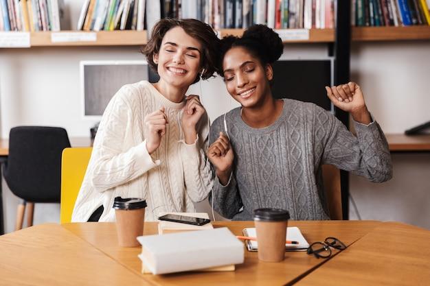Duas alegres jovens estudantes estudando na biblioteca, ouvindo música com fones de ouvido