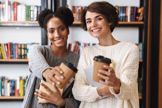 Duas alegres jovens estudantes estudando na biblioteca, segurando livros, bebendo café