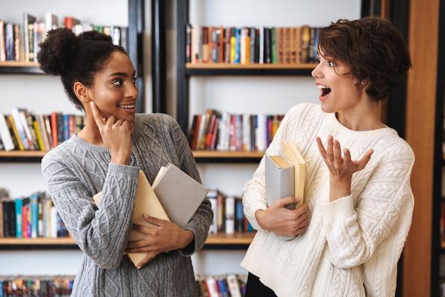 Duas alegres jovens estudantes estudando na biblioteca, segurando livros, conversando