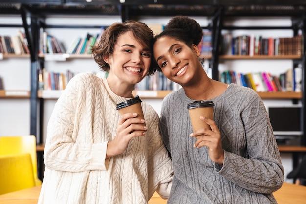 Duas alegres jovens estudantes estudando na biblioteca, tomando café