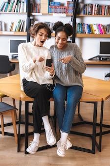 Duas alegres jovens estudantes estudando na biblioteca, usando telefone celular e fones de ouvido