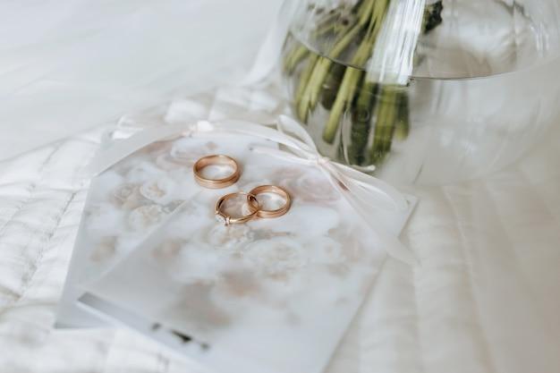 Duas alianças de casamento e um anel de noivado repousam em um convite com fundo de flores