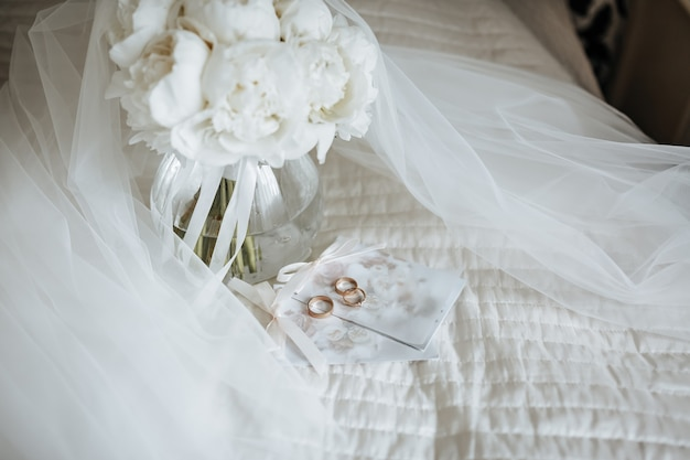 Duas alianças de casamento e um anel de noivado repousam sobre um convite com parede de flores