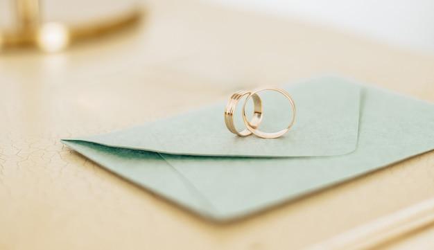Duas alianças de casamento em um convite com fundo dourado