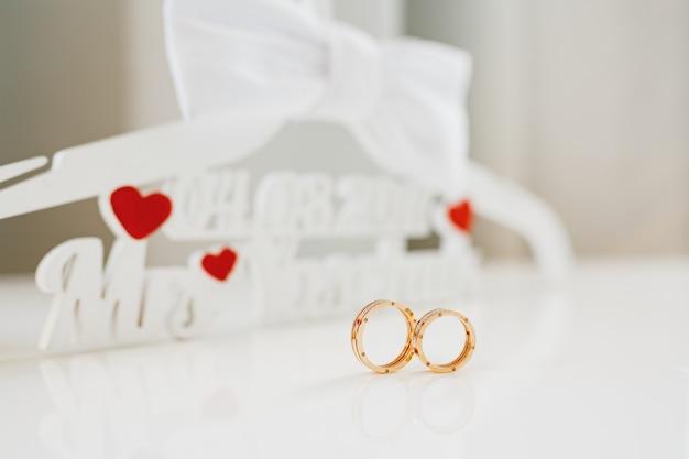 Duas alianças de casamento em um fundo de letras de espuma branca e corações vermelhos