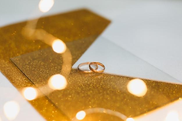 Duas alianças de casamento em um fundo dourado.