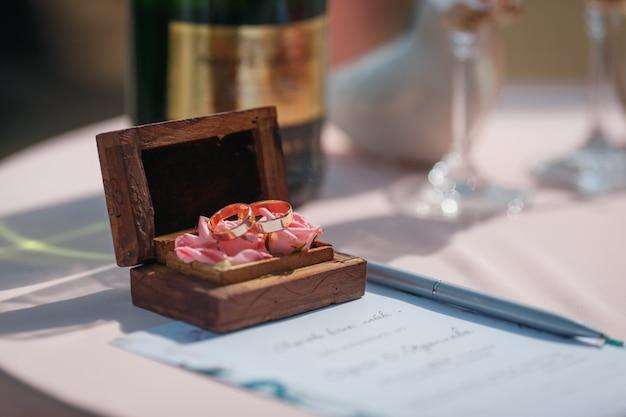 Duas alianças de casamento em um lindo caixão de madeira com musgo verde