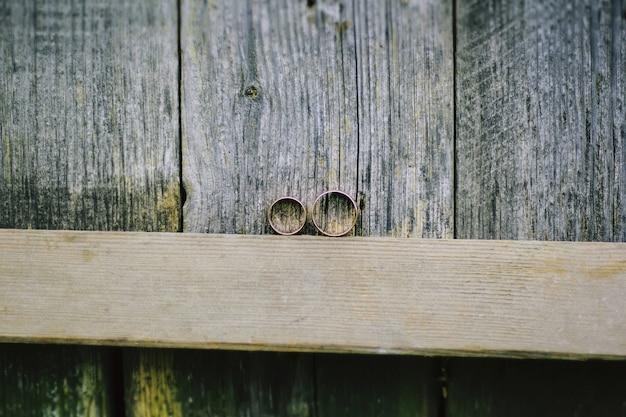 Duas alianças de casamento em um pedaço de madeira. foto rústica e elegante.