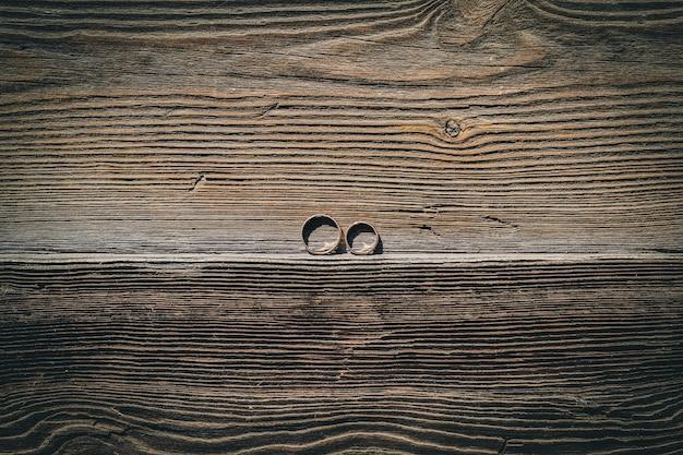 Duas alianças de casamento em um pedaço de madeira.