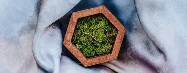 Duas alianças de casamento em uma caixa de madeira com um musgo de planta em um fundo de tecido roxo