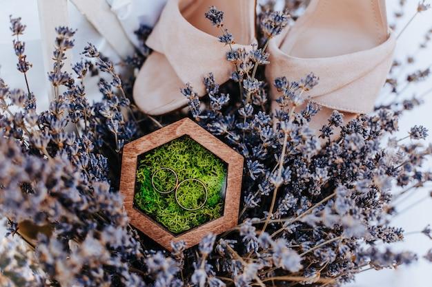 Duas alianças de casamento em uma caixa de madeira com uma planta de musgo em um fundo de flores roxas de lavanda