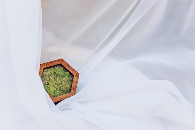 Duas alianças de casamento em uma caixa de madeira com uma planta de musgo em um véu branco