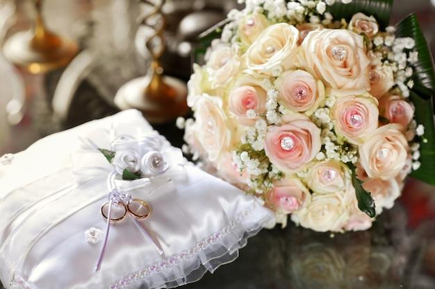 Duas alianças de ouro exibidas em uma almofada branca com um elegante buquê de rosas cor de rosa decorado com joias facetadas em um conceito de amor, compromisso e romance
