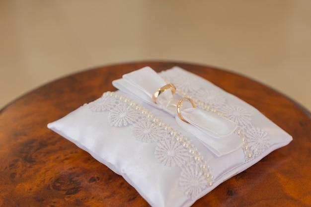 Duas alianças de ouro sobre um travesseiro.