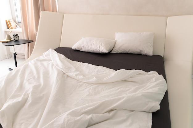 Duas almofadas brancas em cama grande em quarto de hotel