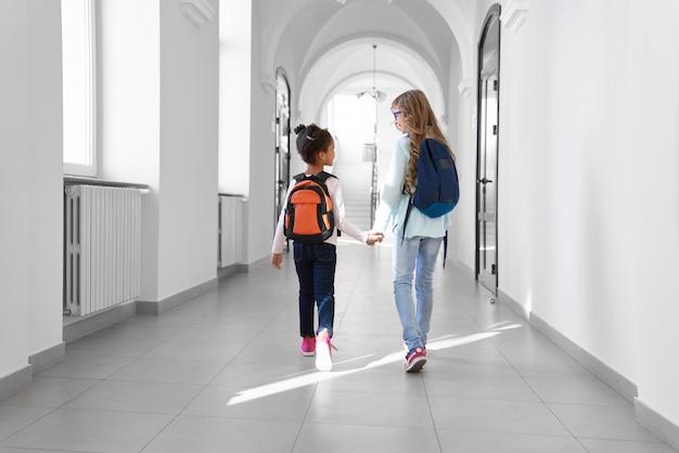 Duas alunas em jeans e tênis com mochilas andando no corredor de luz longa depois das aulas.