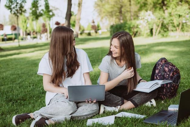 Duas alunas estão sentadas no parque na grama com livros e laptops, estudando e se preparando para os exames. educação a distância. foco seletivo suave.