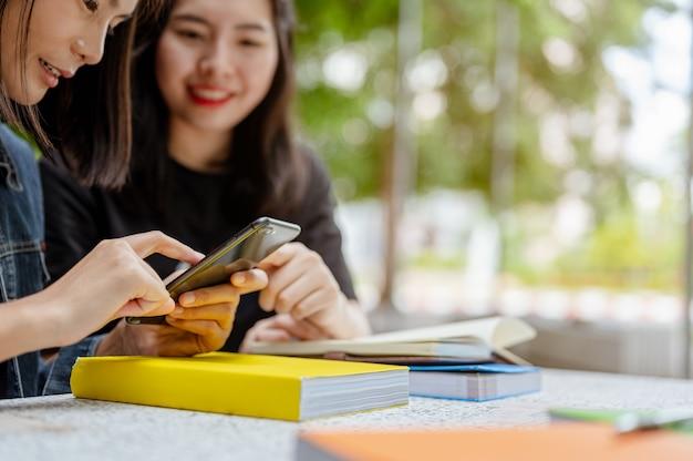 Duas alunas estavam usando um telefone para encontrar informações sobre seus estudos livros de conhecimento