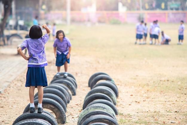Duas alunas jogam pedra-papel-tesoura nos pneus de decoração