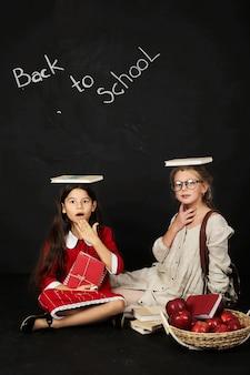 Duas alunas lindas namoradas felizes se divertir sentado com livros na cabeça Foto Premium