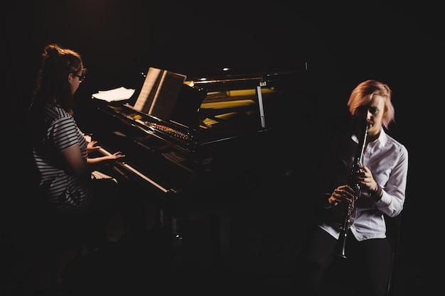 Duas alunas tocando clarinete e piano