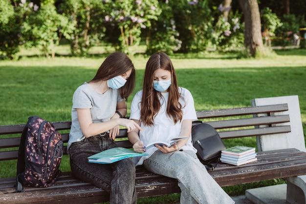 Duas alunas usando máscaras médicas protetoras se preparam para os exames em um banco do campus. educação a distância. foco seletivo suave.