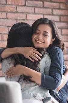 Duas amigas a abraçam