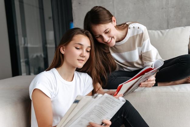 Duas amigas adolescentes alegres sentadas em casa no sofá lendo revistas