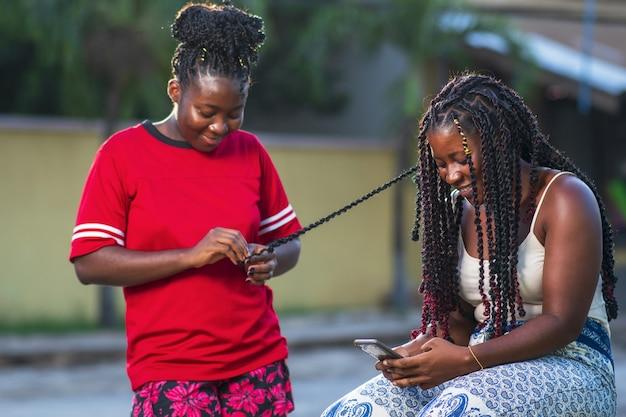 Duas amigas afro-americanas sorrindo e fazendo tranças no cabelo ao ar livre