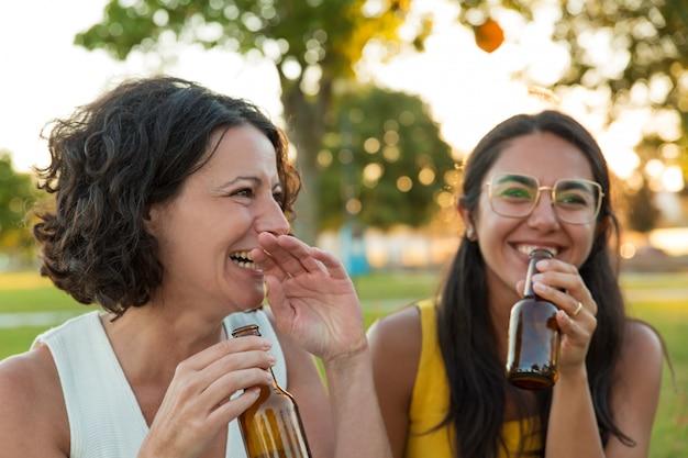 Duas amigas alegres bebendo cerveja e se divertindo